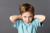stubborn young kid teasing, covering closed ears, ignoring parents